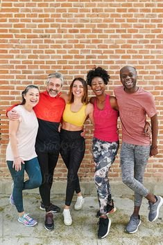 Diverse group of fit friends in sportswear smiling while standing arm in arm together outside in front of a brick wall